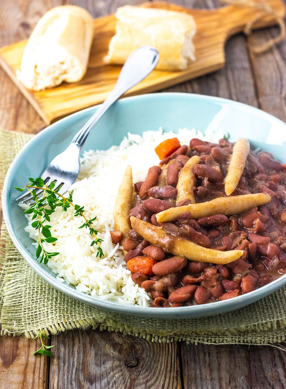Jamaican stew peas with spinners, carrots, on steamed rice in a blue bowl, stainless steel fork, garnished with thyme sprigs on a brown wooden background with cutting board and bread