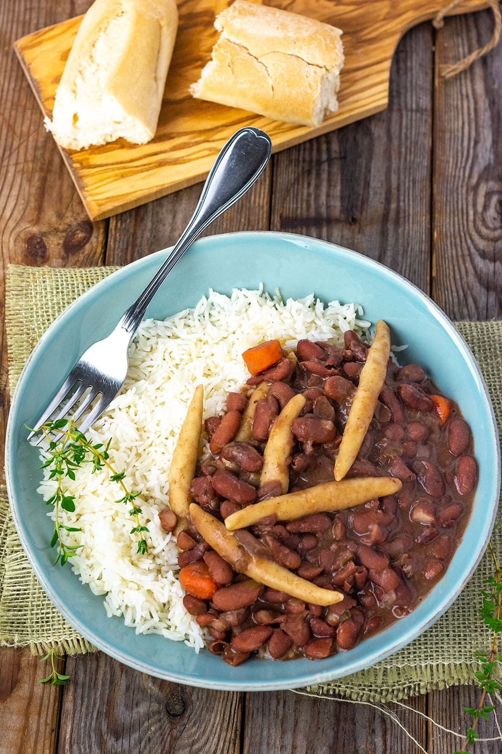 Jamaican stew peas with spinners, carrots, on steamed rice in a blue bowl, stainless steel fork, garnished with thyme sprigs on a brown wooden background with cutting board and bread overlay