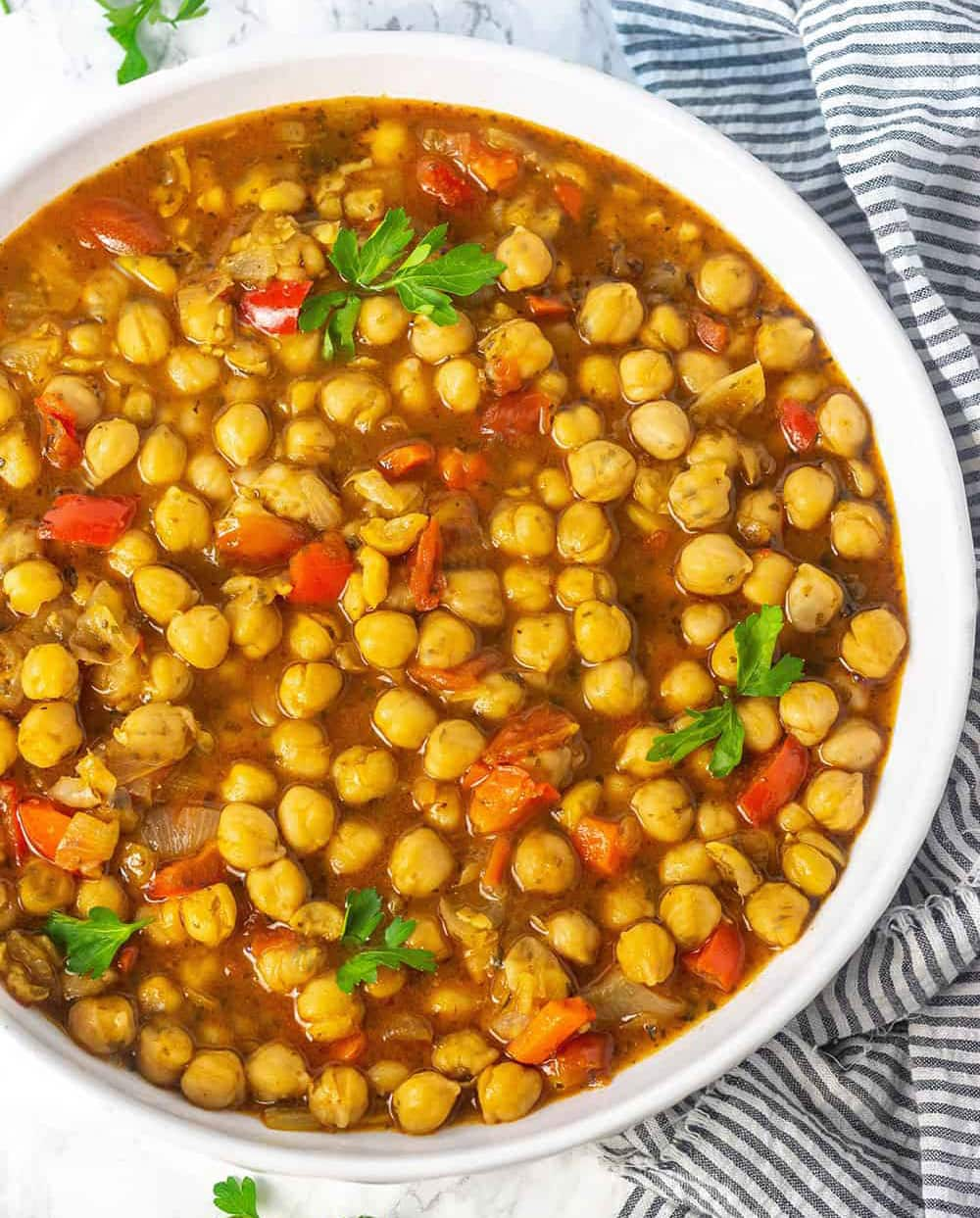 Vegan Chickpea Stew overlay in a white bowl. Cooked with tomatoes, bell pepper and carrots.