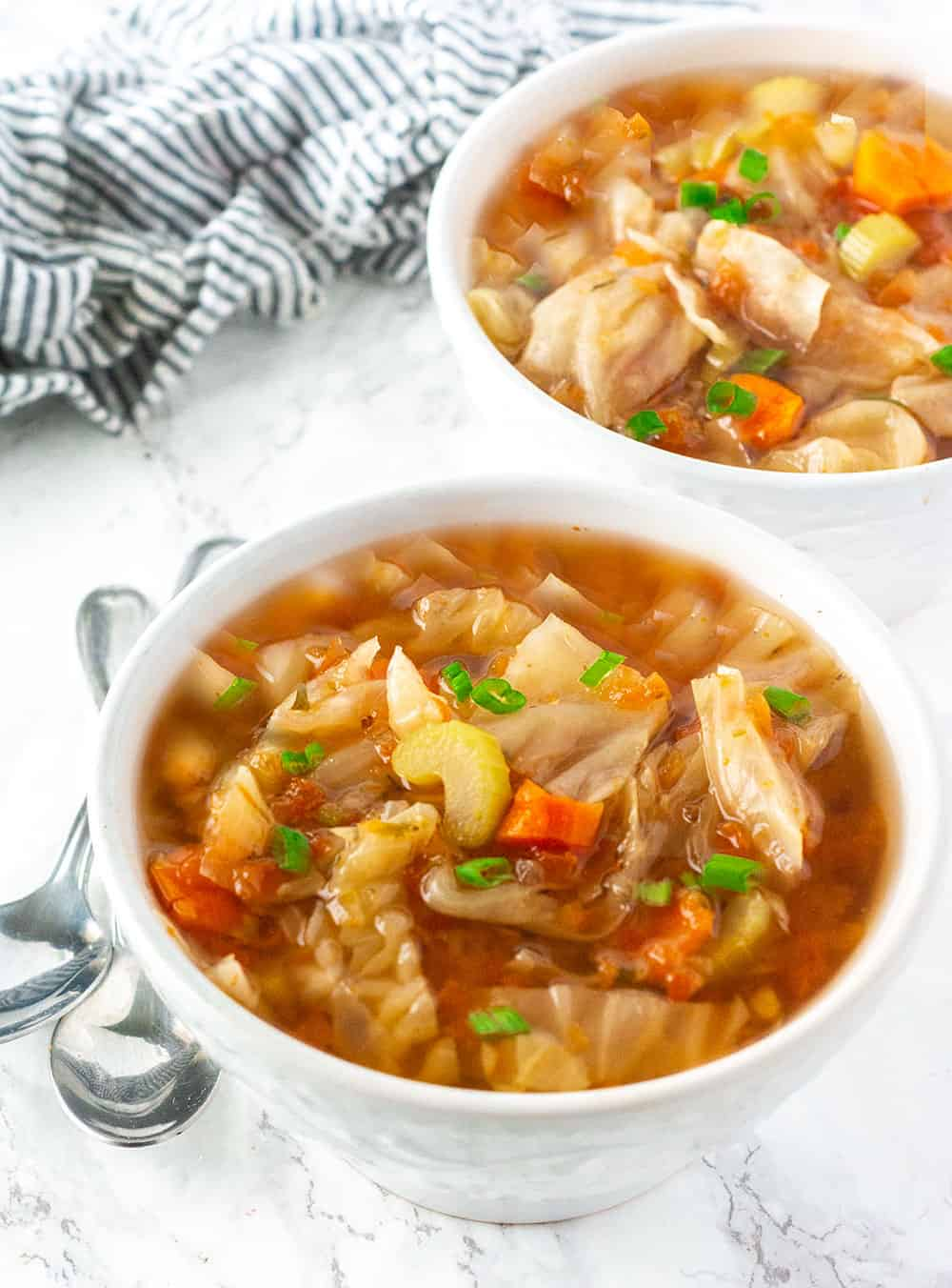 Best Vegan Cabbage Soup in white bowls with cabbage, carrot, and scallion