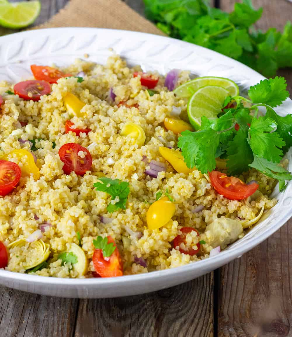 Best Quinoa Salad With Artichoke, tomatoes, onion and chopped cilantro in a white bowl