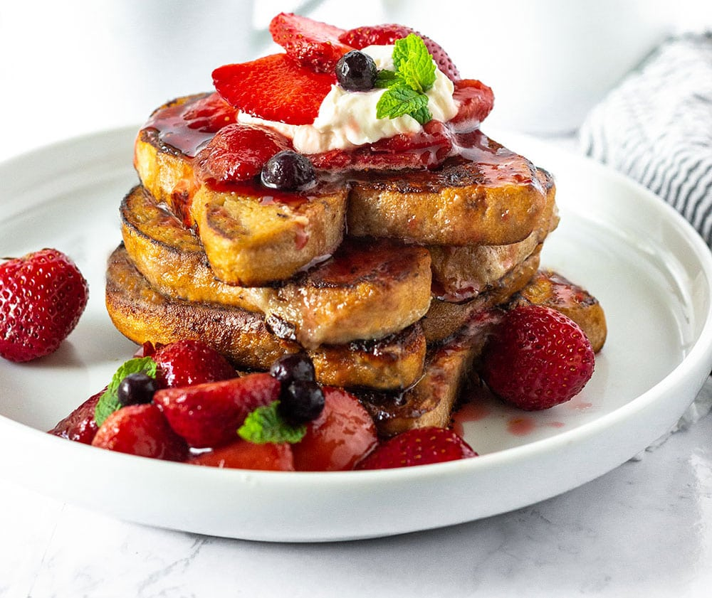 best vegan french toast stacked on a white plate with strawberry sauce