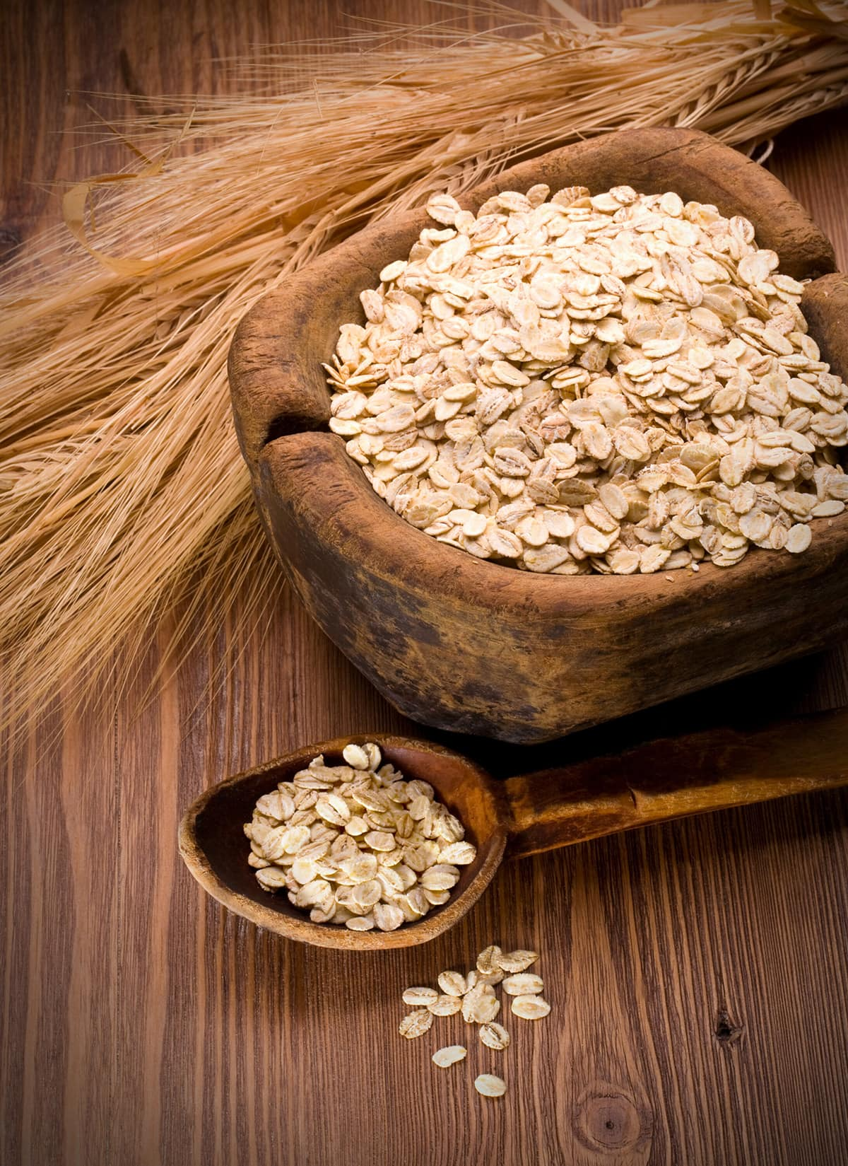 oatmeal in wooden bowl and wooden spoon