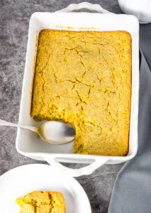 Vegan Gluten-Free Cornbread Casserole overlay in a white casserole pan with a spoonful of cornbread casserole