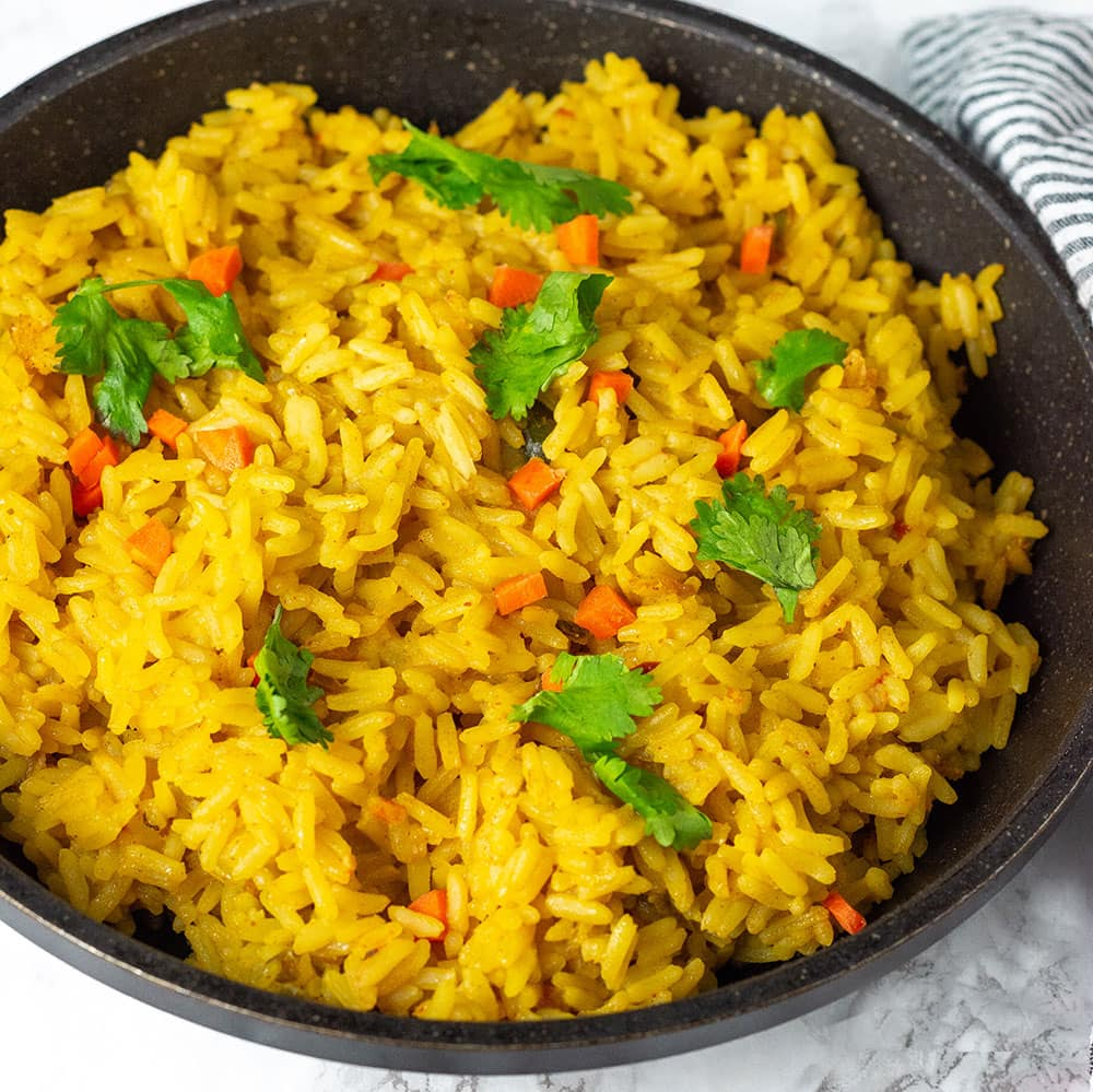 Turmeric coconut rice made with seasoned coconut milk, flavorful and easy to prepare in a black saucepan on a white background