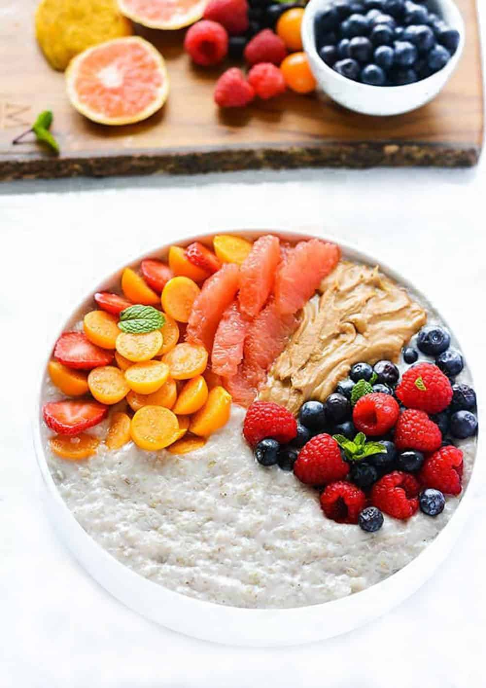 Overhead photo of Porridge Buckwheat in a White bowl with berries and almond butter
