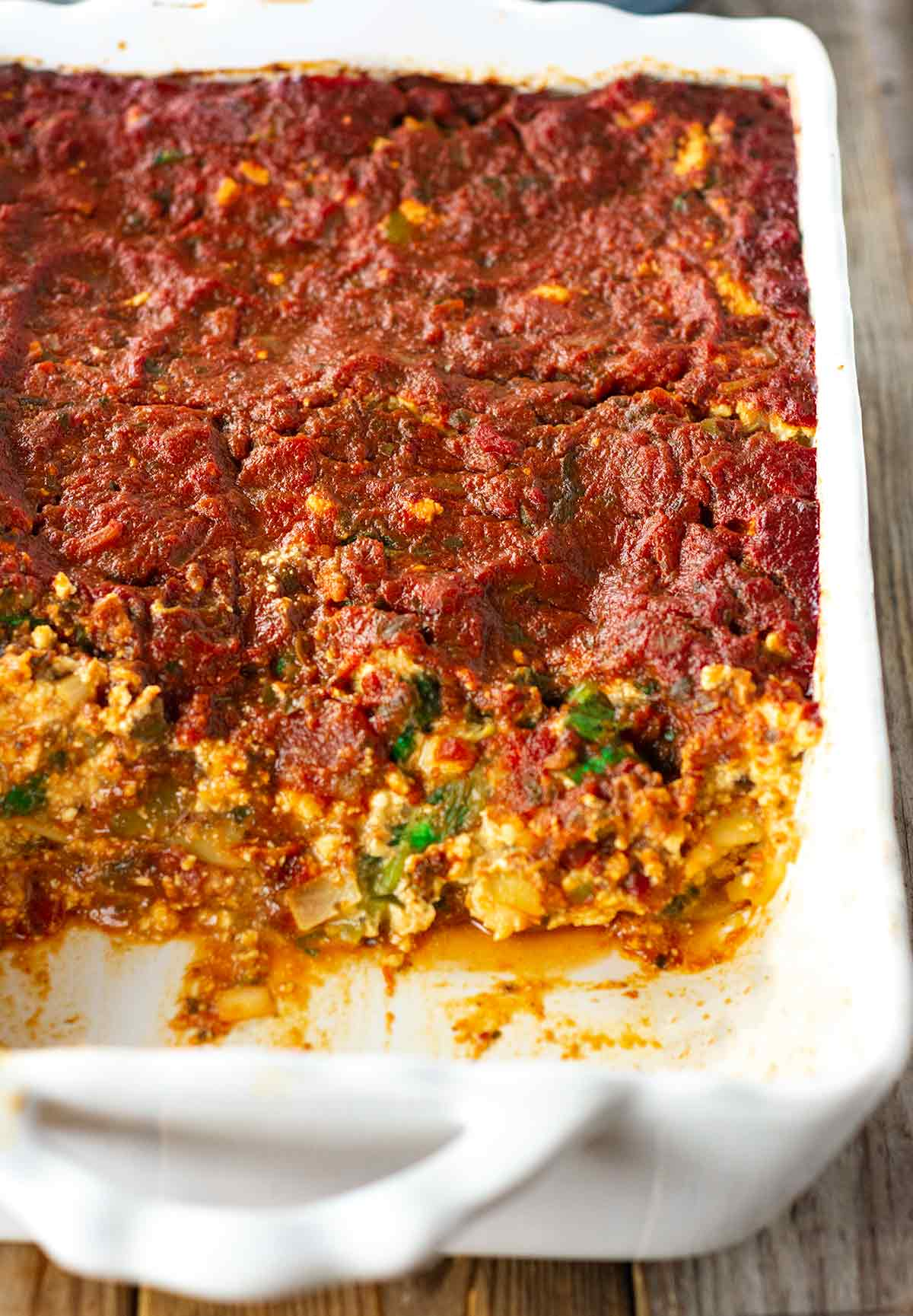 overlay lasagna in a white casserole pan on a wooden backgroun
