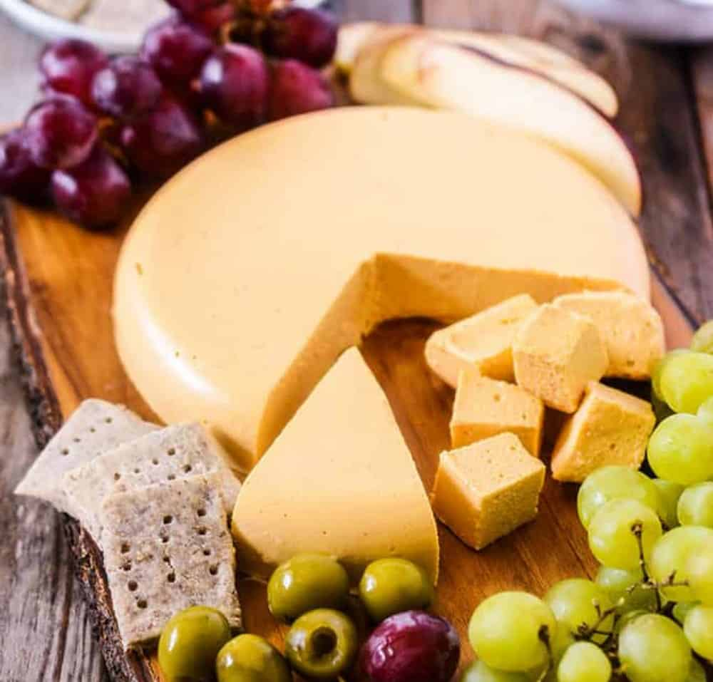Vegan Cheese Board with cubes of cheese, crackers, olives, grapes