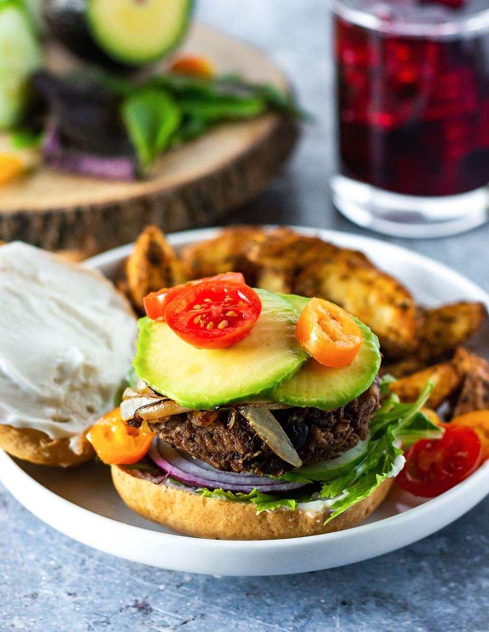 vegan black bean burger on gluten-free vegan bun, with mayo, red onion, caramelized onion, avocado, tomatoes