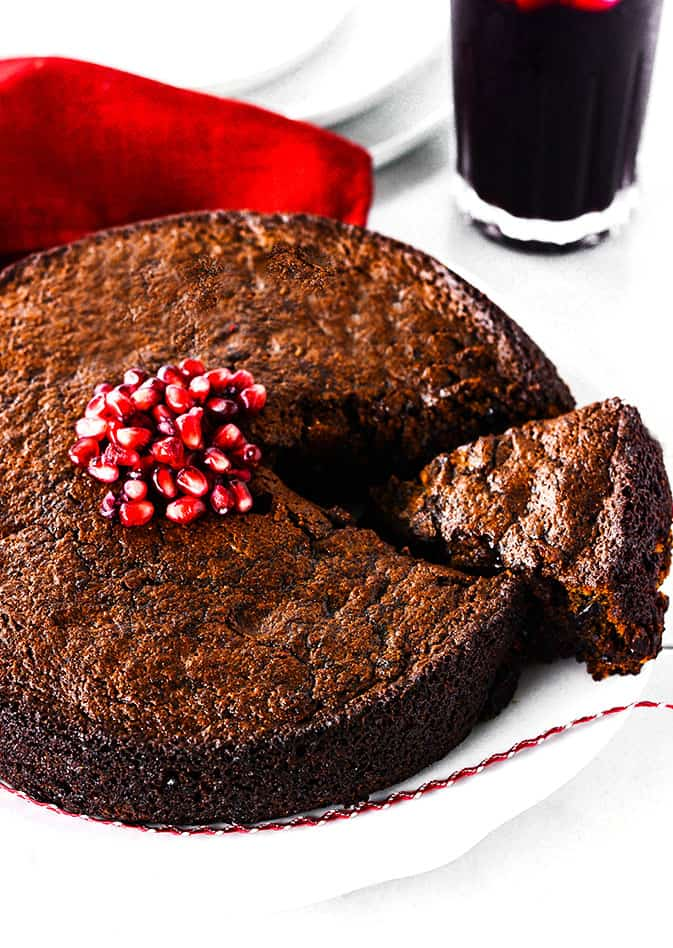 Jamaican Christmas Cake Recipe on a white background topped with pomegranate arils