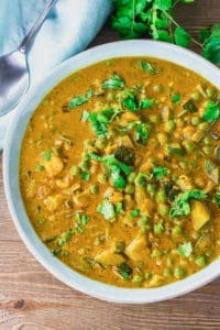 Zucchini and Green Peas Coconut Curry in a blue bowl