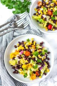 Southwestern Salad with Avocado Dressing on 2 white plates