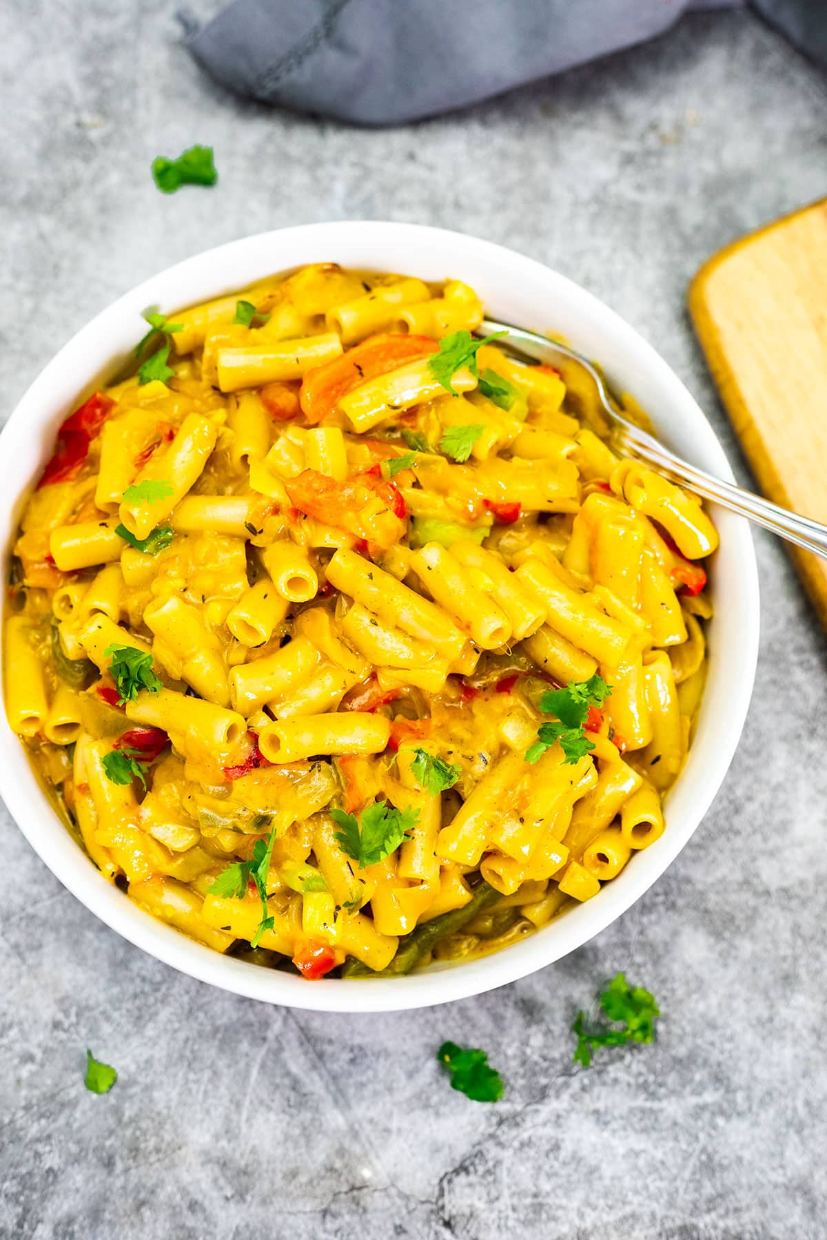 vegan rasta pasta salad on a white plate with a skillet in the background