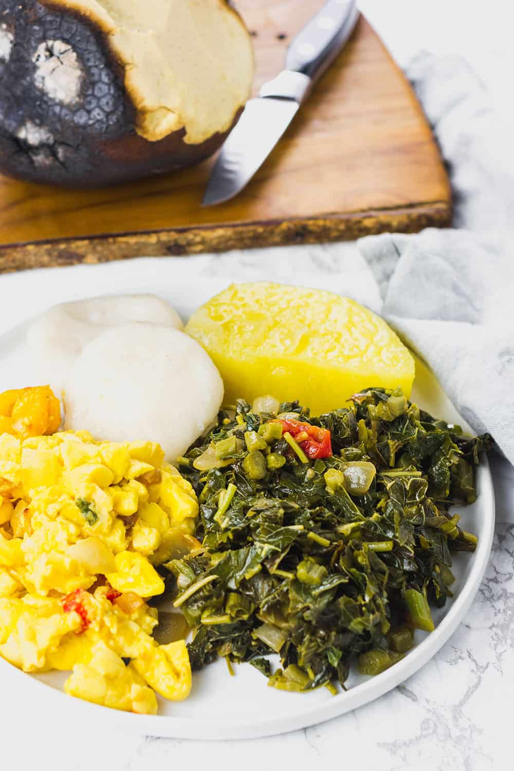 Jamaican Callaloo on white plate with ackee, yellow yam, dumplings and roast bread fruit