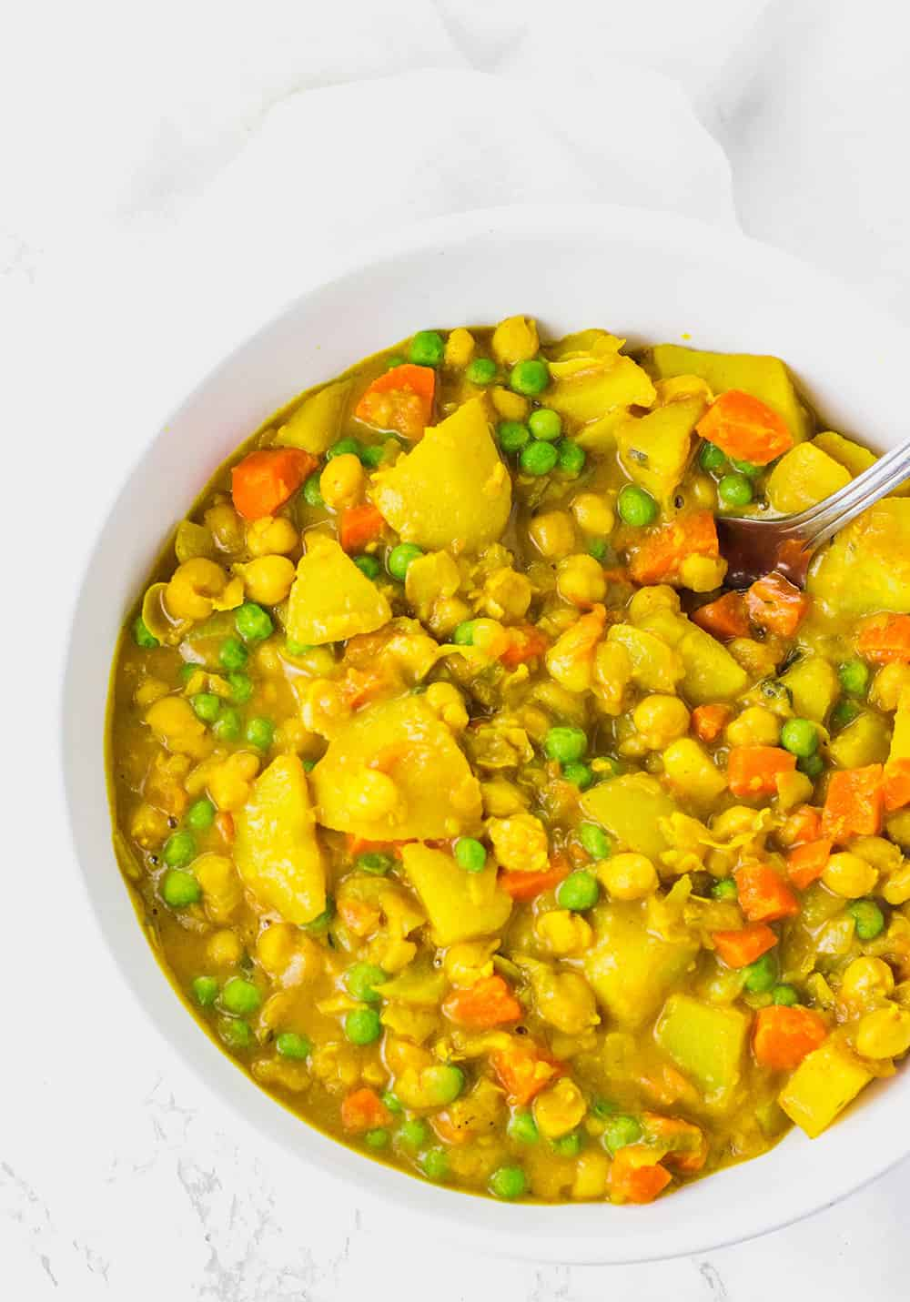 Curry Potato, Chickpea, Carrot and Green Peas Curry in a white bowl