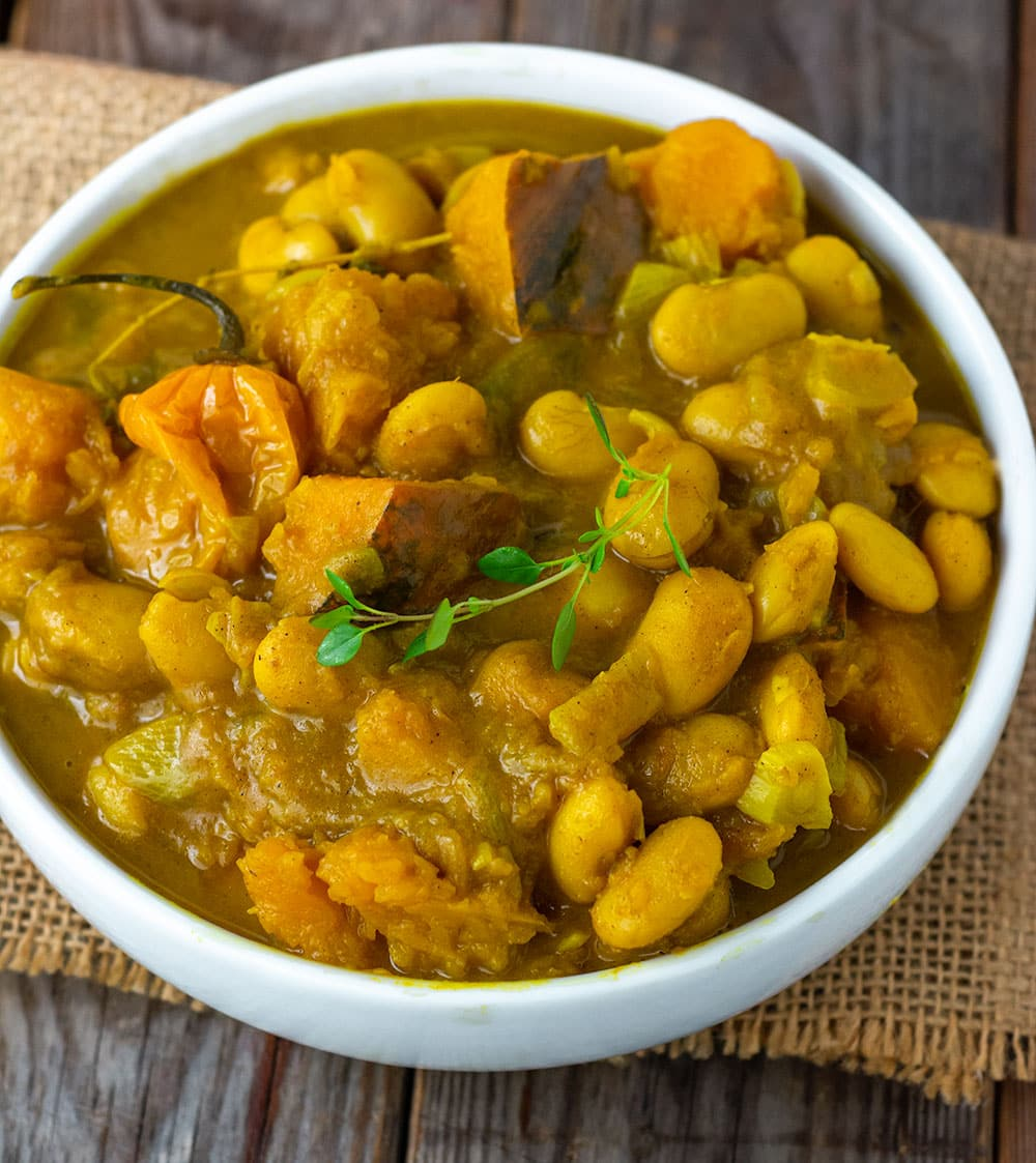 jamaican-style pumpkin curry with butterbeans, garnished with yellow scotch bonnet pepper, and a sprig of fresh thyme in a white bowl on a burlap napkin. In the background is an orange covered pot on a wooden cutting board beside yellow rice in a white bowl and a wooden background.
