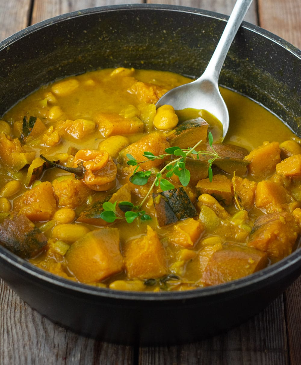 Easy Jamaican Pumpkin curry in a black saucepan with silver serving spoon garnished with a sprig of thyme on a wooden background