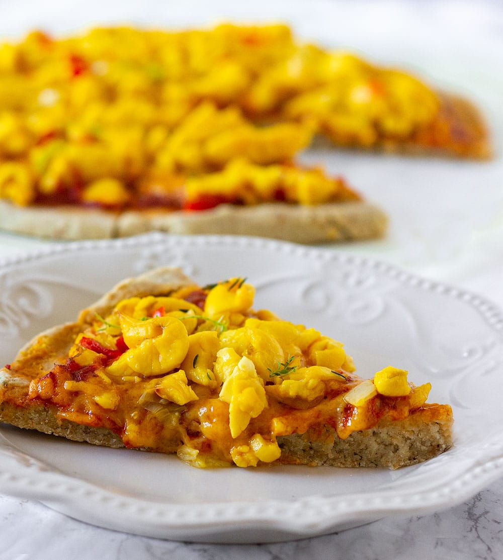 vegan ackee pizza, slice in the foreground on a white plate with the remaining pizza in the background.