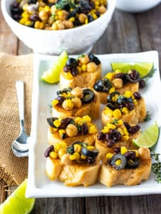 Chickpea Salad Crostini on a white platter topped with corn, chickpea, black bean and olives