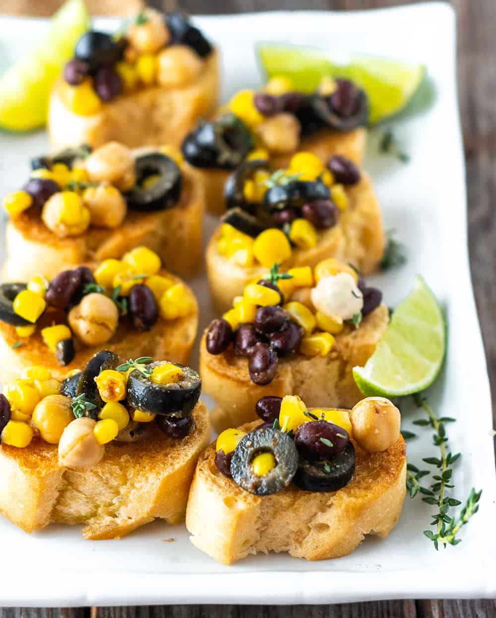 easy crostini chickpea salad recipe on a white platter with lime and thyme garnishes