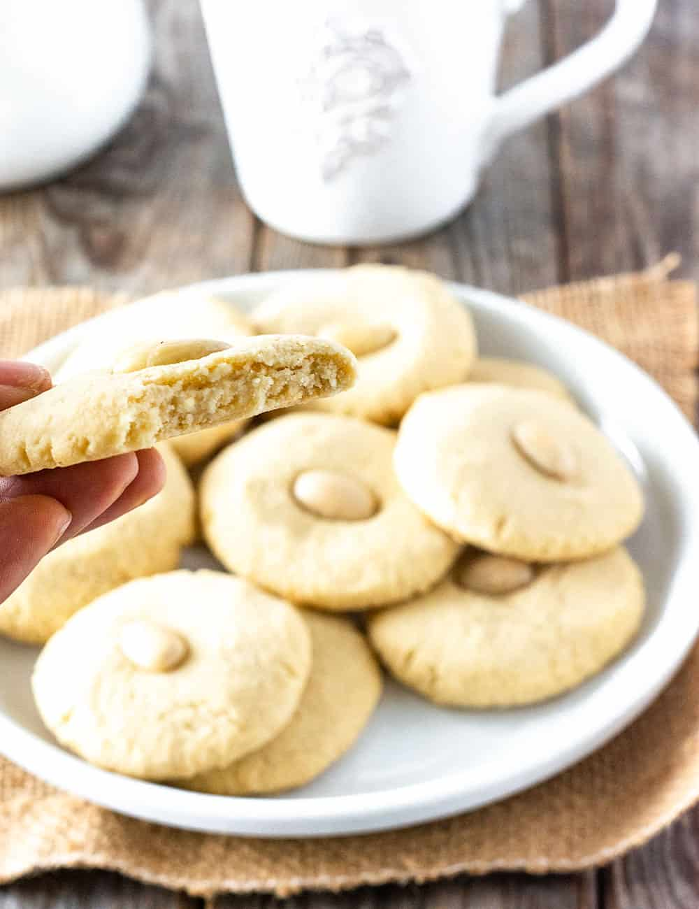 Chinese almond cookies on a white plate with my hand holding a half a cookie