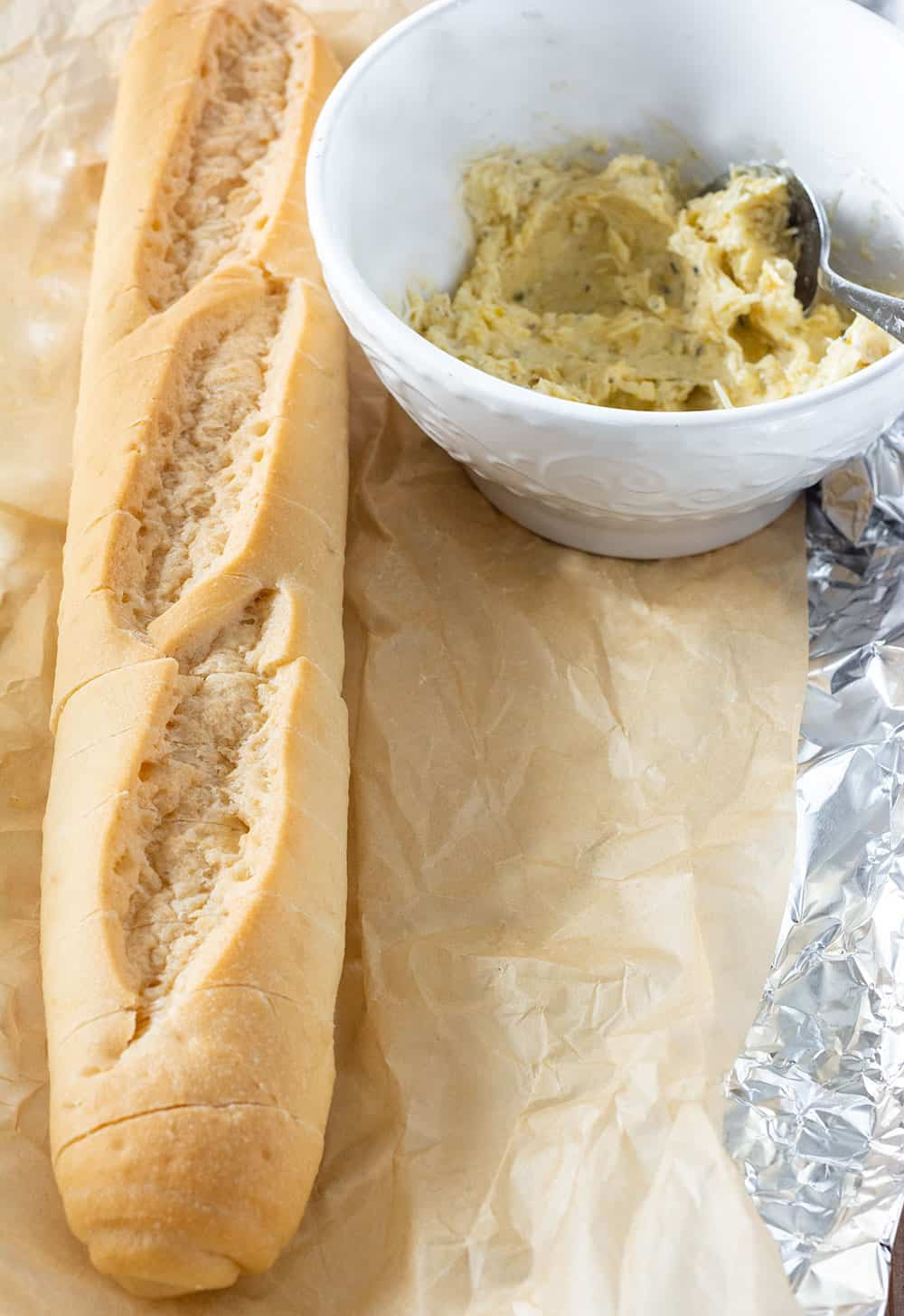 Garlic bread ingredients, baguette and garlic butter in a white bowl