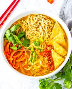 Gluten-free ramen noodle. spiralized carrot, fried tofu, red pepper slices , in a white bowl with cilantro leaves, red chopsticks on a white background