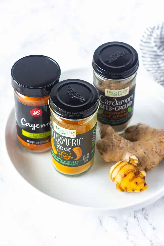 Ingredients for golden milk turmeric tea, cayenne pepper, turmeric, cardamom, ginger in spice botttles
