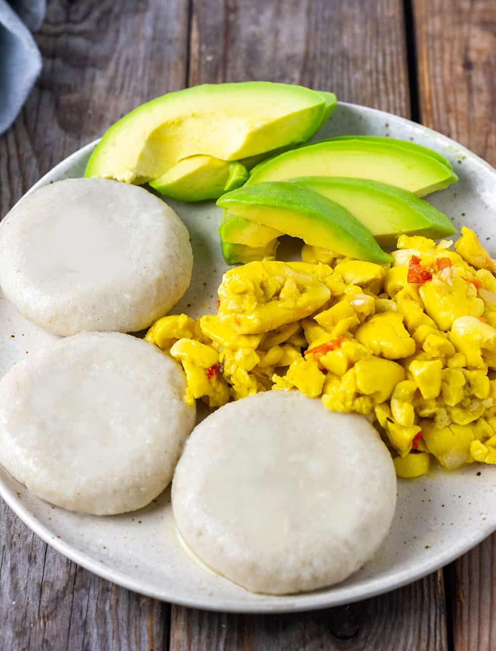 Jamaican Boiled Dumplings (Gluten-Free) on a beige plate with ackee and avocado slices