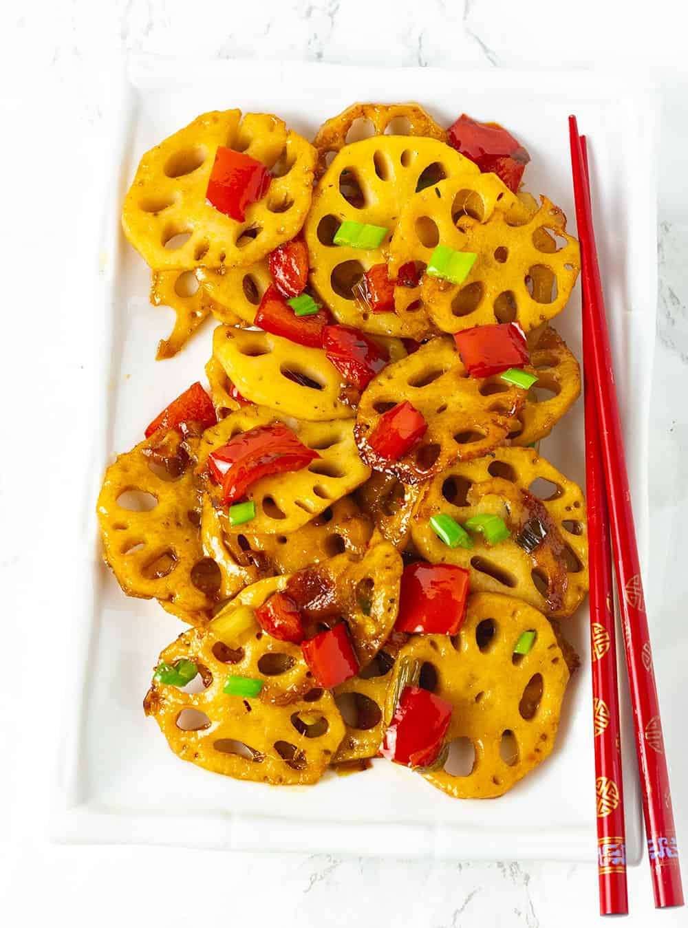 Stir fry lotus on a white platter with red chopsticks, red pepper, green onions