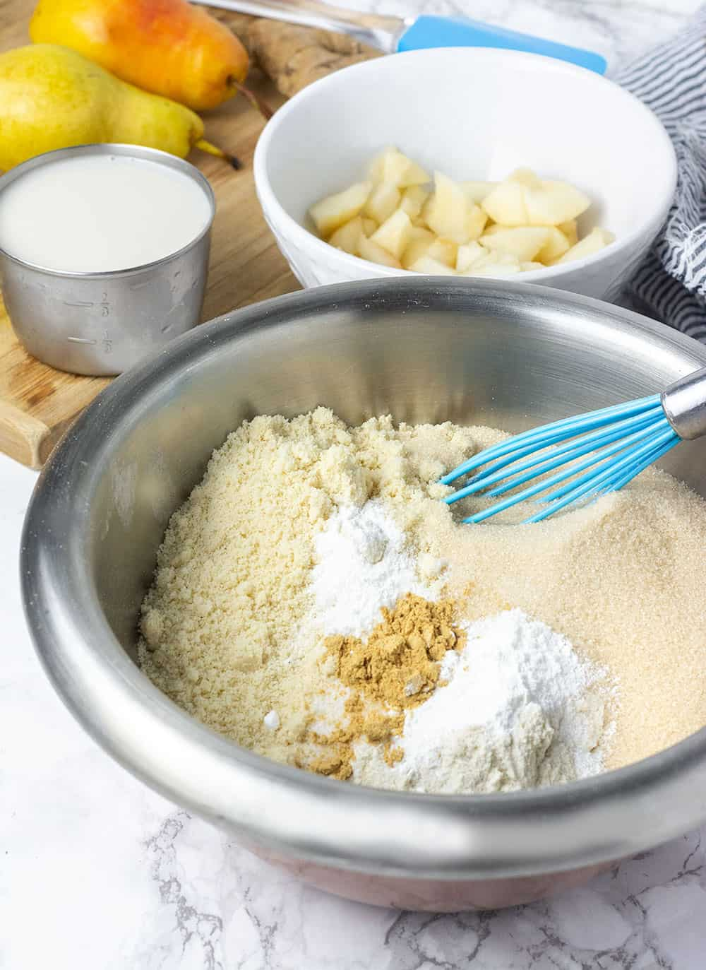Ingredients for vegan-gluten-free pear muffins in a bowl with chopped pear, almond milk