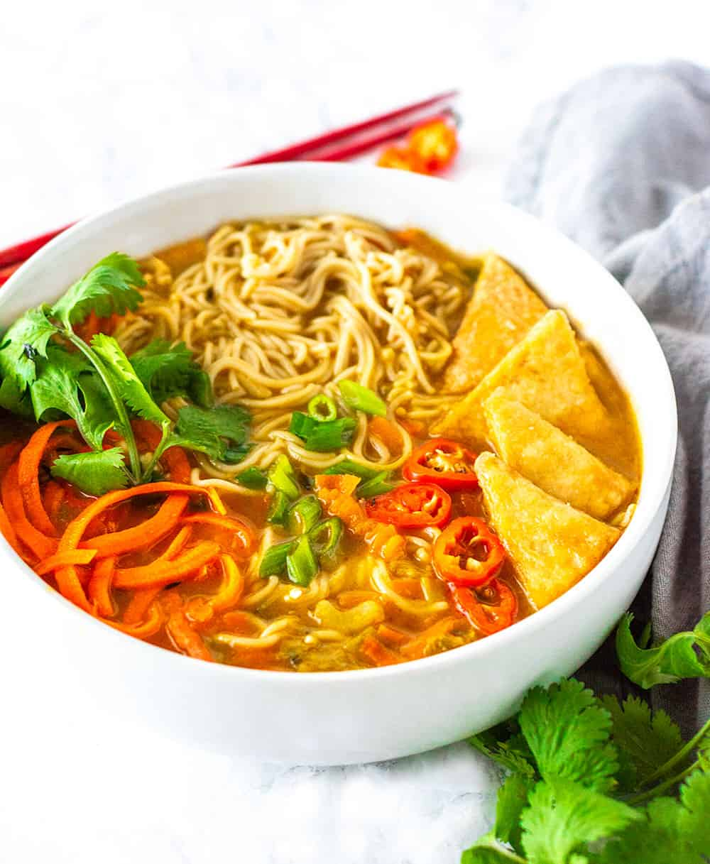 Gluten-free ramen noodle. spiralized carrot, fried tofu, red pepper slices , in a white bowl with cilantro leaves, red chopsticks on a white background and gray napkin