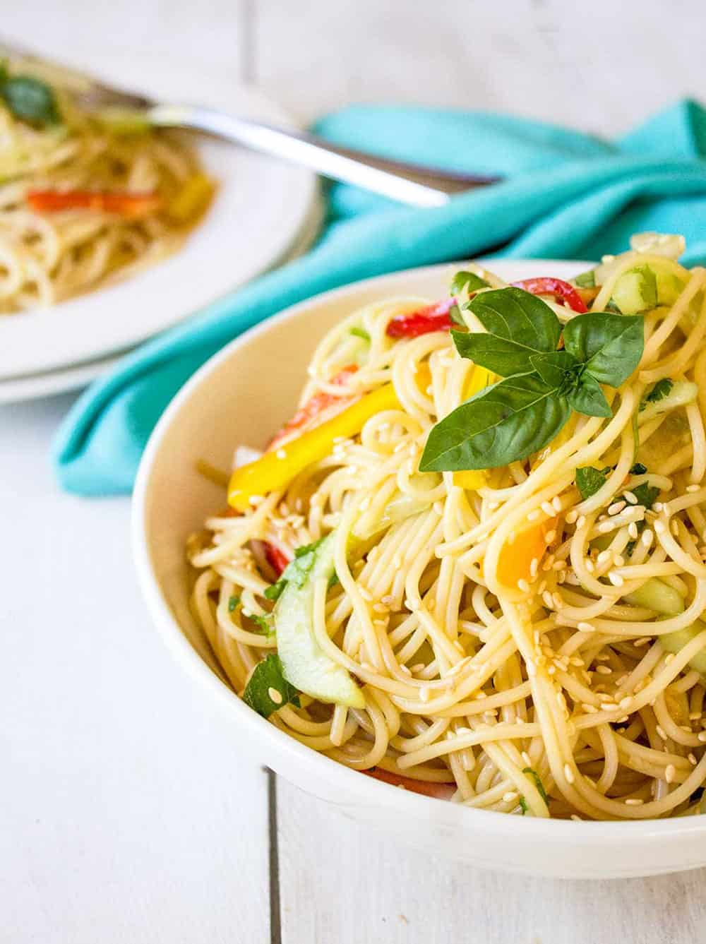 Thai Pasta Salad with red and yellow bell pepper and garnish with basil on a white background with blue hand towel