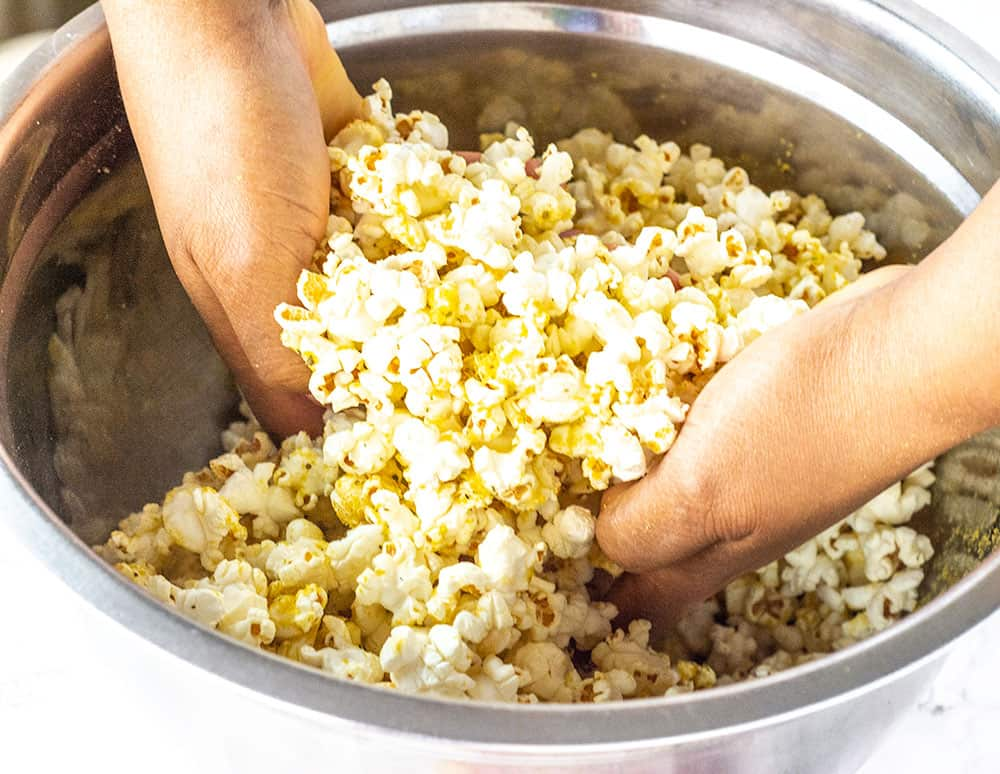 Vegan popcorn being tossed with seasonings in a stainless steel bowl, using both hands