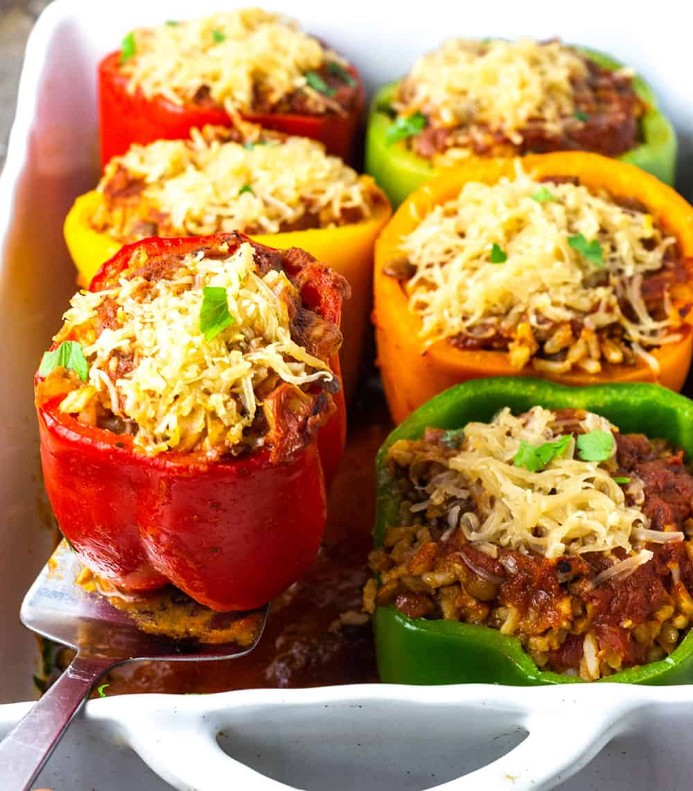 Vegan stuffed bell peppers multicolors peppers, red, yellow, orange and green stuffed with lentil rice, and topped with vegan cheese shreds in a white casserole dish in marinara sauce