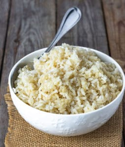 Learn how to cook brown rice, cooked brown rice in a white bowl with a spoon