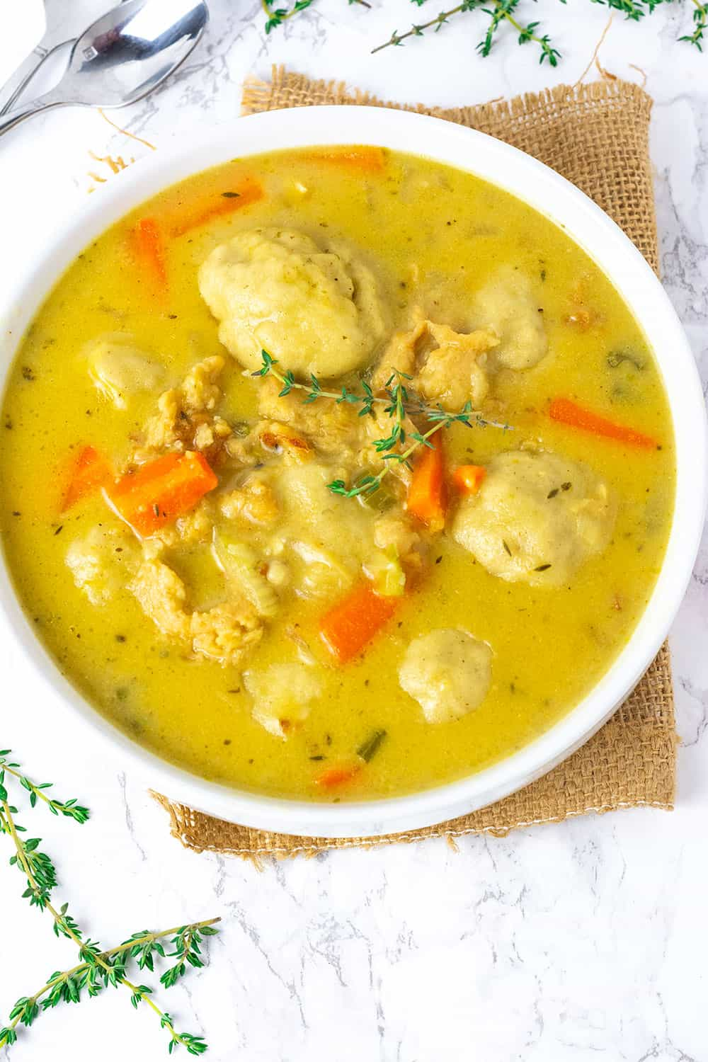 instant Pot vegan chicken dumplings with gluten-free vegan herb dumplings in a white bowl with carrots and garnish with thyme
