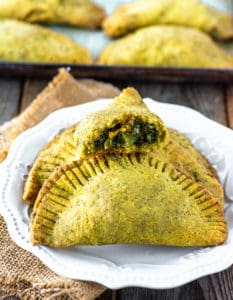 Jamaican callaloo patties. 3 patties on a white plate with baking sheet in the background with more patties on a wooden background