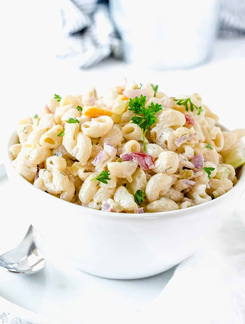 Vegan macaroni salad with red onions, parsley in a white bowl