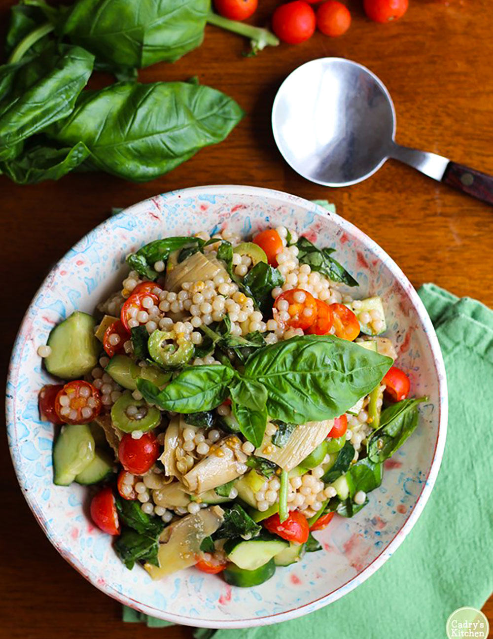 Overhead shot of Israeli couscous salad with cucumber, tomatoes garnish with basil in a funfetti bowl