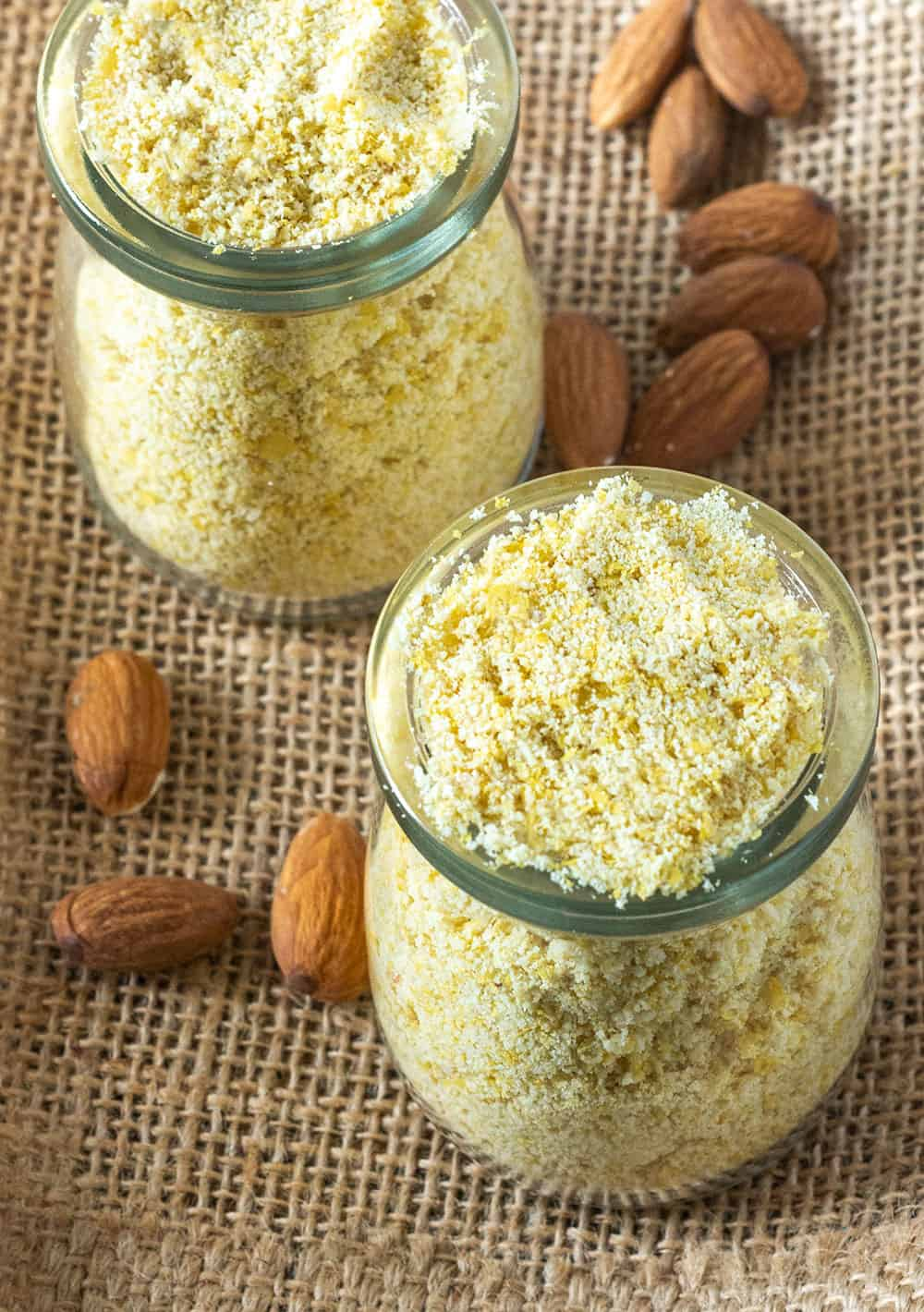Overlay Vegan parmesan cheese mix in 2 glass jars on a wooden background