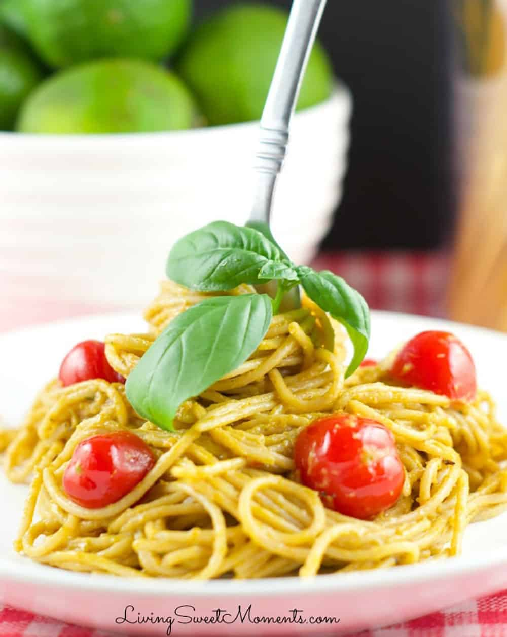 Roasted red pepper and avocado pasta on a white plate with a fork in the center, garnished with cherry tomatoes and basil