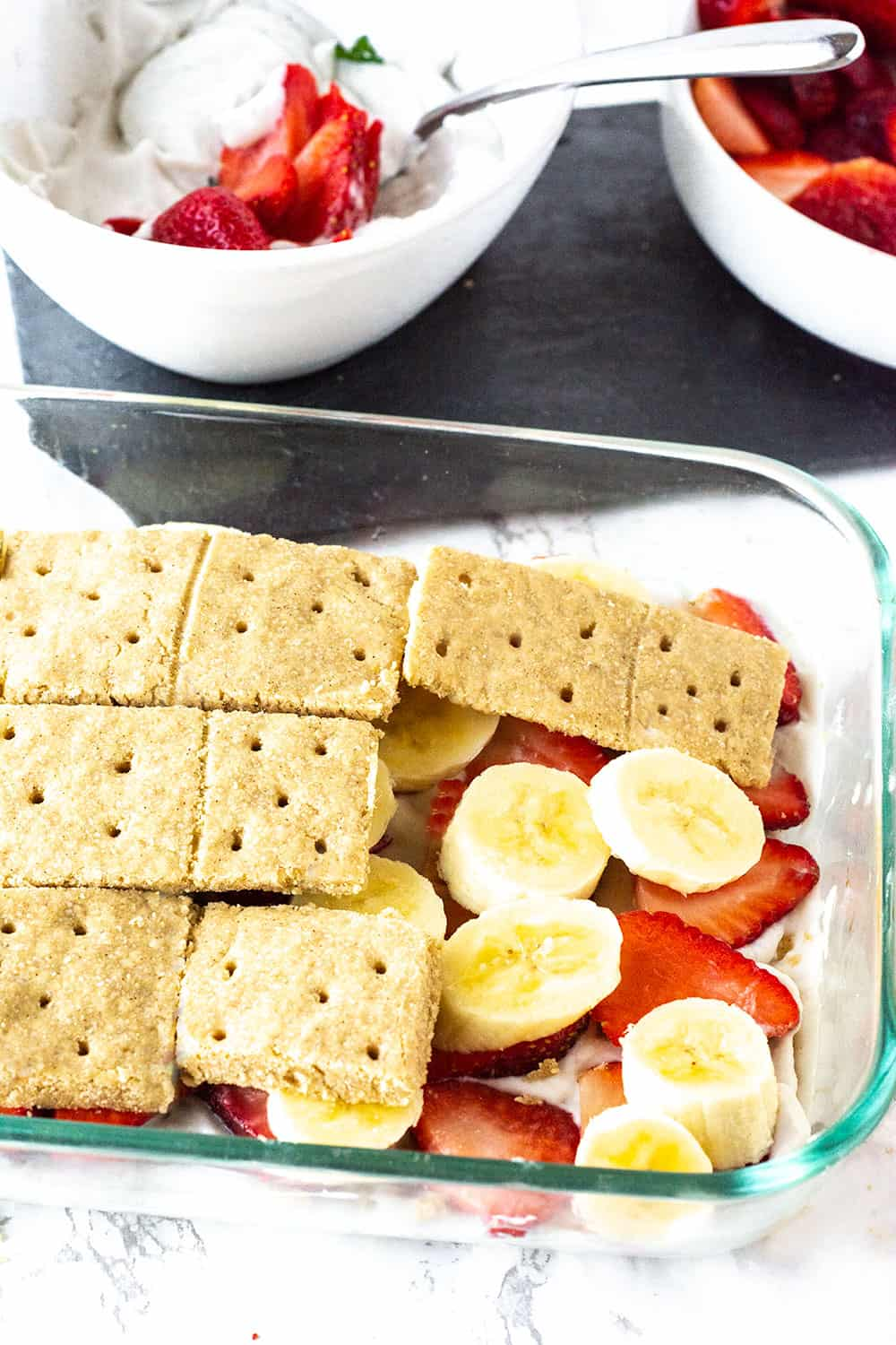Step by step strawberry icebox cake with graham cracker, strawberry and bananas