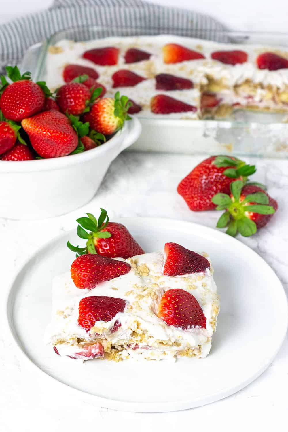 Strawberry Icebox Cake made with graham crackers, coconut whipped cream, strawberries, banana, a slice on a white plate topped with strawberies