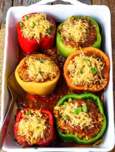 vegan stuffed bell peppers overlay, red, yellow, orange, green stuffed with rice and cooked lentils in tomatoes sauce, topped with shredded in a tomato sauce