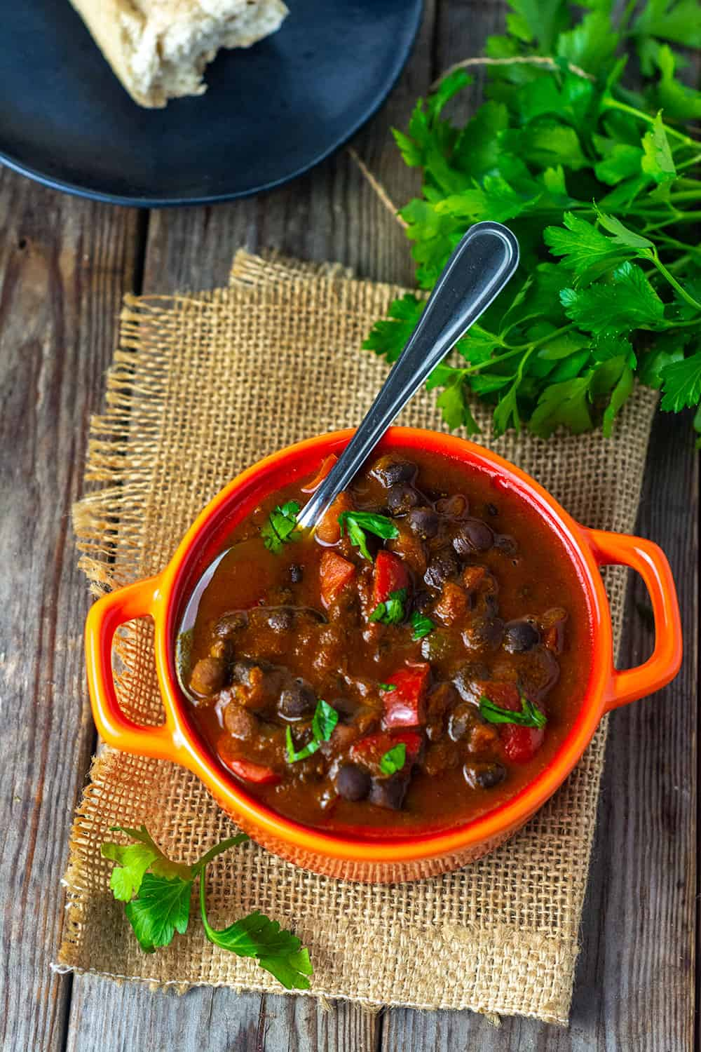 Overhead Black Chickpeas Stew with tomatoes, bell pepper, onion in a vegetable broth, served in a red dish on a wooden background garnished with parsley