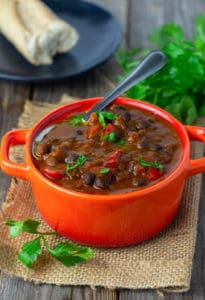 Black Chickpeas Stew with tomatoes, bell pepper, onion in a vegetable broth, served in a red dish on a wooden background garnished with parsley
