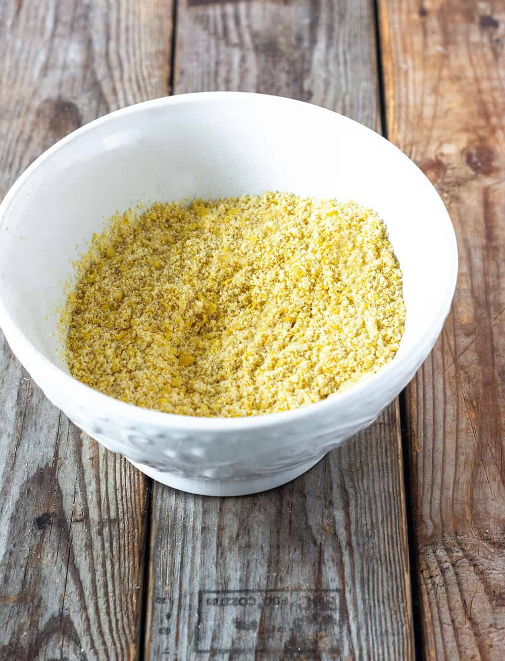 Vegan parmesan cheese mix in a bowl on a wooden background