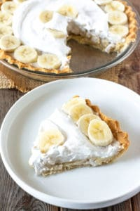 Banana cream pie in pie plat topped with coconut whipped cream and fresh banana slices with a slice in a white plate on a wooden board