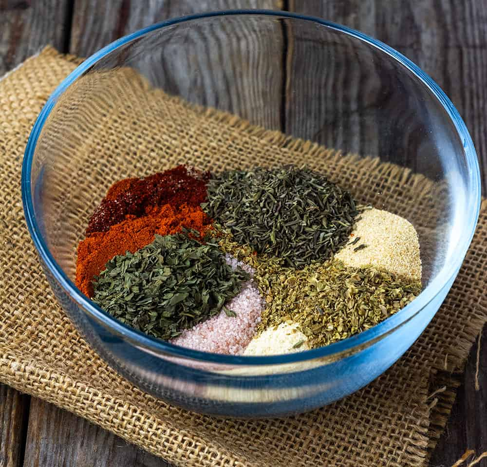 Creole seasoning mix in a glass bowl on brown wooden background with each spice.